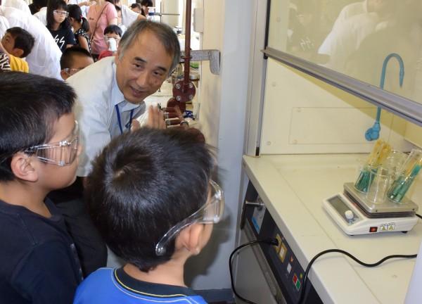 試薬に漬けた電子基板の様子を観察する子どもたち