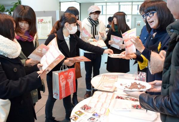 フェアトレードチョコレートの意義や味を知ってもらおうと、名古屋学院大学の学生たちに振る舞う原田さとみさん(右)たち