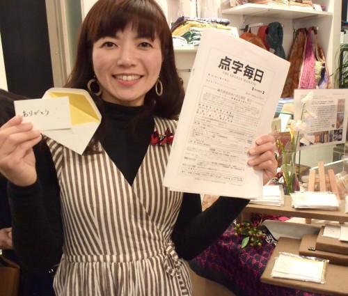 「Join the Dots」プロジェクトをスタートさせた吉井由美子さん。右の点字新聞が左の封筒に